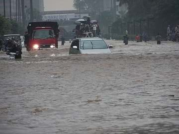 Cars and people amidst the flooded streets of Jakarta in Indonesia on January 17, 2013.