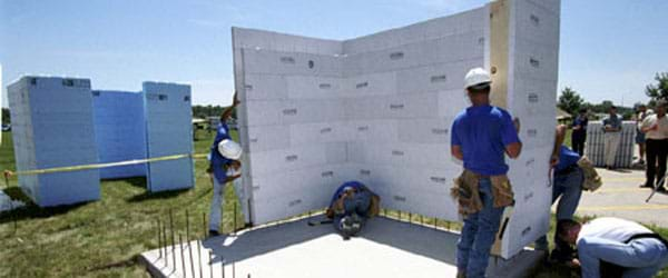 The image shows a group of engineers assembling a concrete foundation for a building.
