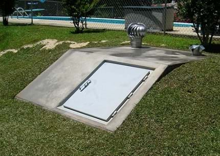 The image shows a concrete slab with a door and vents, in the ground. This is an opening to an underground structure, which can provide a safe location during a tornado.