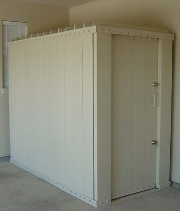 The image shows a small room, resembling a shed, inside a building. It is equipped with steel walls, a concrete foundation, and a removable door.