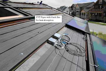 Photo shows flat plastic pipes covering an angled roof surface with two shiny black panels installed over some of them, plus some wires and electrical outlet boxes. A labeled arrow says: PVT pipes with black fins for heat absorption.
