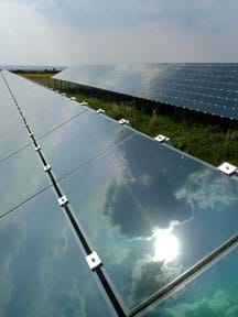 Photo shows an array of solar panels with the sun, sky and clouds reflected in them.