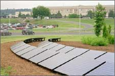 Two curved rows of solar panels on a tilted rack on the ground in a landscaped area.