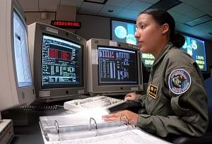 A young woman at a desk with three computer monitors (a space system operator) runs through a checklist during GPS satellite operations.