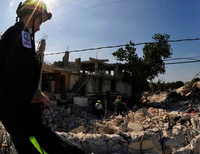 A man in a safety helmet looks into a pit and field of crumbled rubble from destroyed buildings.
