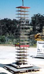 Photo shows a tall tower made of platforms and columns placed on a wider base located in an open parking lot.