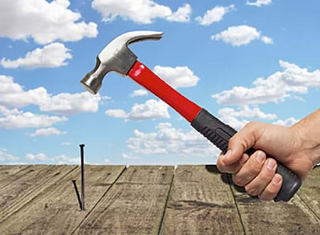 Photograph of a person using a hammer on a nail with a cloudy blue sky background.