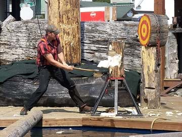 A lumberjack with an axe splitting wood.