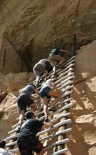 People climbing a ladder at the Mesa Verde National Park.