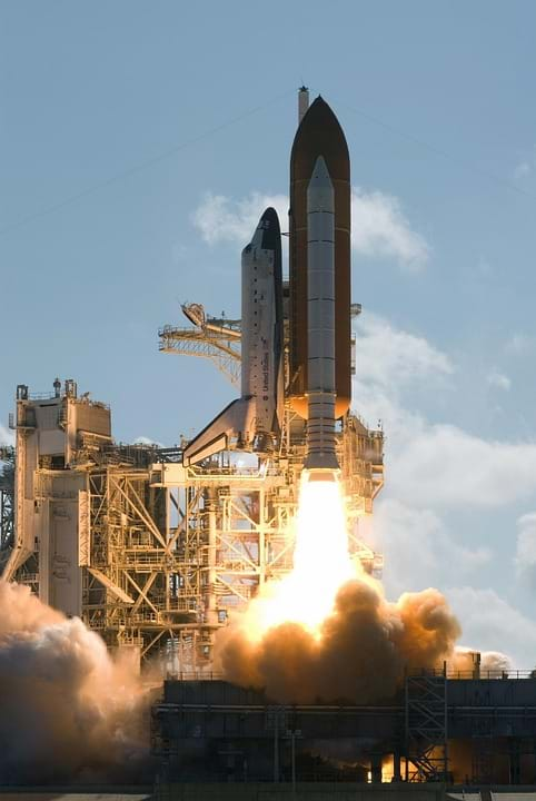 Photo shows a US space shuttle lifting off with much fire and smoke seen below the rocket.