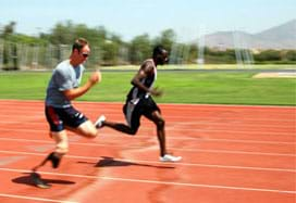 Two men run side-by-side on a track, one with a prosthetic leg.