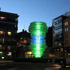 A photograph shows an illuminated green and blue (somewhat) tornado-shaped five-story light sculpture in a courtyard with seven-story buildings nearby.