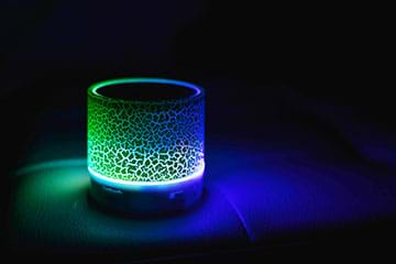 A photograph taken in darkness shows a cylindrical night-light with a crackle finished that glows green and blue.