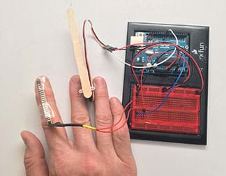 A photograph shows a flex sensor taped to the index finger of hand, which is connected to a breadboard and Arduino microcontroller. A Popsicle stick held between the hand's middle and ring fingers is also connected to the Arduino.