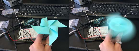 Two photographs show the same scene. In the background, a desktop setup of a spinning motor circuit on a wired breadboard connected to Arduino. In the foreground: A hand holds a small motor with a four-blade, pinwheel-shaped fan made of angle-folded blue paper sticky notes attached to it. On the left, the motor is off so you can clearly see the pinwheel fan. On the right, the motor is on and the fan is a blur (spinning).