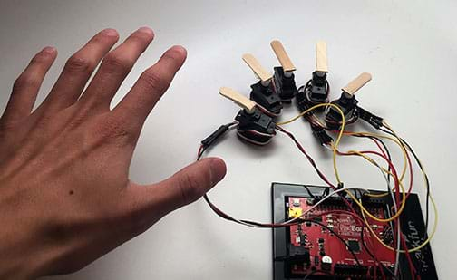 A photograph shows five servos each connected by wire to an Arduino. On each servo is hot-glued a portion of a popsicle stick, making each like a finger, and together, mimicking a human hand. For comparison, an open hand is next to the five servos.
