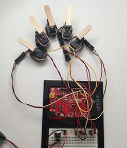 A photograph shows an Arduino and breadboard hooked up to five servo motors, each with glued-on partial Popsicle stick heads, mimicking a five-fingered human hand. Same setup as Figure 3.