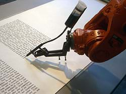 A photograph shows the end of an orange industrial robot arm that is writing text with an ink pen on a roll of paper.