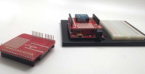 A photograph shows an Arduino microcontroller with an attached breadboard. An Arduino shield is stacked on top of the Arduino board so the pins on the shield are pushed into the pins on the Arduino.