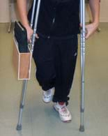 A photo shows a boy using a pair of crutches. Attached to the outer side of one crutch below the hand support is a container—a flat wooden box with the top side open; it contains a notebook.