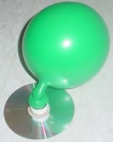 A photograph of a model hovercraft; a blown up balloon is attached to a bottle cap, which is glued to a CD.
