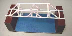 A photograph shows a truss-style straw bridge (Howe-Kingpost design) made of plastic drinking straws and clear tape spanning the gap between two wooden blocks, ready for testing.