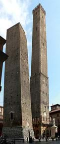 "A photograph shows the ""twin towers"" of Bologna, Italy—two side-by-side masonry towers, ~150 feet high and ~300-feet high, both with bases wider than their tops. The shorter one in the foreground leans a little."
