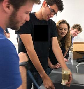Four students set up a quicksand experiment over a lab sink using the vacuum filter with three students observing.