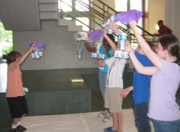 A photograph shows students standing in a circle preparing to test their disaster relief packages from the initial height, above their heads.