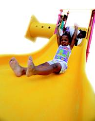 A photo of girl sliding down a playground slide.