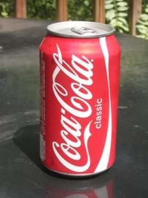 Photo shows a pop-top aluminum can of Coca-Cola.