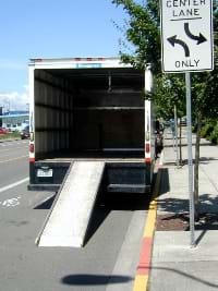 A photograph shows the back of a big truck with a ramp from the road up to the interior floor of the truck.