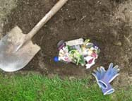 Photo shows view from above of a hole in the ground filled with assorted trash (vegetable peelings, packaging wrappers, tissue, egg shells, tea bag, can lid, plastic lid), and a shovel and gloves nearby.