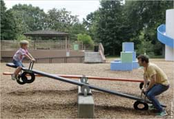 A photograph shows a playground see-saw with a boy at one end, up in the air, and a man at the other, lower end of the long plank.