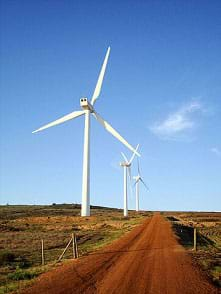 A photograph shows three very tall, three-bladed white wind turbines along a rural dirt road in Cape Town, South Africa.