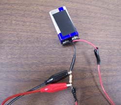 Photo shows a 9V battery connected by wire to a resistor placed between two probe leads (red and black).