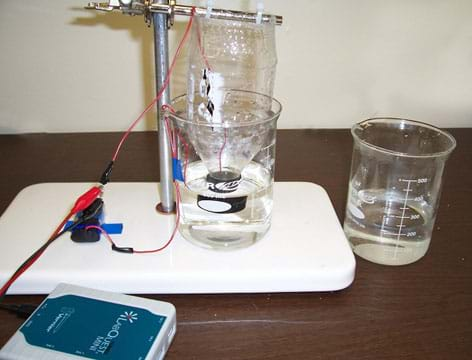 Photo shows a desktop set-up with the top half of a plastic beverage bottle suspended upside down into fluid in a glass beaker with wires running from inside the bottle and beaker to the battery, resister and probes.