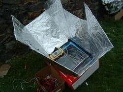 Photo shows a solar oven composed of a box with a solar panel on top, surrounded by angled foil-covered reflective panels.