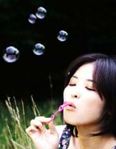 Photo shows a girl blowing bubbles using a plastic bubble wand.