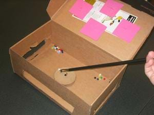 Inside an open box, you can a device holding a bead near a small hook.