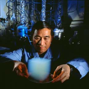 A man (Peter Tsou) in a darkened laboratory uses two hands to hold a plate in front of him. On the plate rests a ~6 x 6-inch cube of aerogel that looks like a floating cube-shaped bluish-milky white cloud (blurry edges).