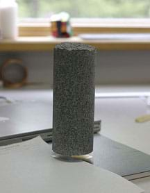 A photograph shows a two-inch square block of aerogel holding up a 4-kilogram cylinder of granite with no apparent deformation.