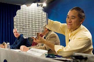 A photograph at a press conference shows a man (Peter Tsou) at a table with three other men, holding up what looks like a shiny, silver round and flat device composed of deep rectangular cells (a stardust sample tray), into which aerogel blocks are placed.