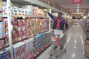 A photograph shows a man pushing a cart in the breakfast cereal aisle of a grocery store