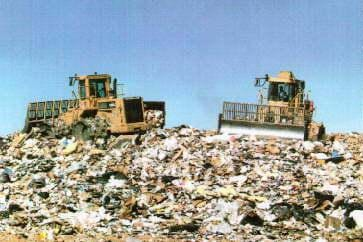 A photograph of a modern landfill - two bulldozers push around a huge pile of trash.