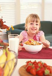 A photograph shows a girl at a table with a bowl of flaked cereal.