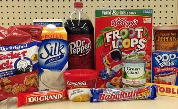 Food items on a grocery shelf: Cracker Jack caramel popcorn in a bag, soy milk in a carton, soda in a plastic bottle, cereal in a box, cereal in a plastic cup, potato chips (Pringles) in a tall cardboard canister with resealable lid, pop tarts in a cardboard box, candy bars in Mylar and paper wrappers, soup in a plastic bowl with a plastic lid.