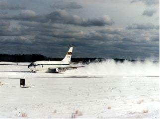 A photograph shows an airplane landing on a snowy runway.