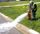 Photo shows a woman using a wrench on a fire hydrant that is spewing water.