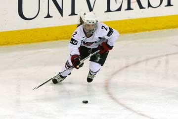 A female hockey player on ice about to hit the puck playing in the Olympics.